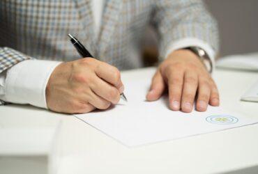 Osoba w garniturze podpisująca dokumenty